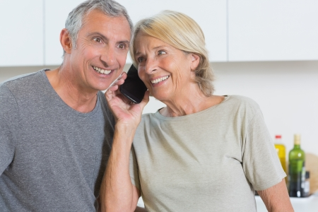 Couple taking a call together in the kitchen photo