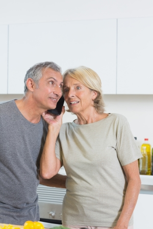 Mature couple listening a call together in the kitchen photo