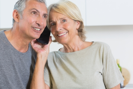 Cheerful mature couple listening a call together in the kitchen photo