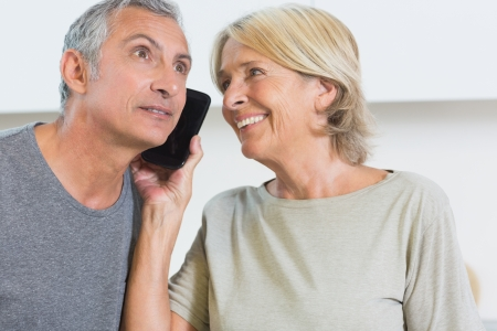 Happy mature couple listening a call together in the kitchen photo