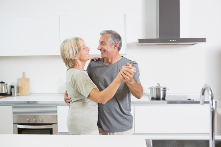 cherishing: Couple dancing together in the kitchen