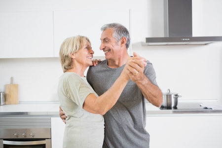Smiling couple dancing together in the kitchen photo