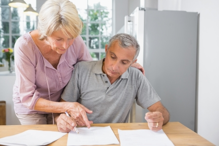 Wife showing where to sign to her husband in the kitchen Stock Photo - 18118368