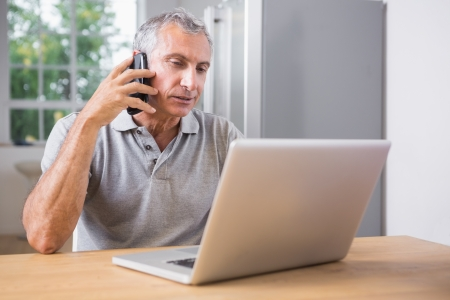 Mature man using his laptop and calling at home