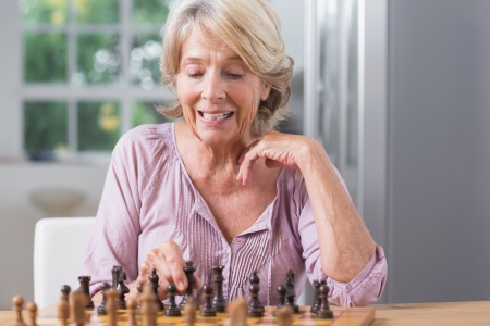 Mature woman playing chess at home photo