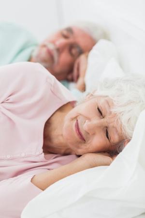 Elderly couple asleep in bed photo