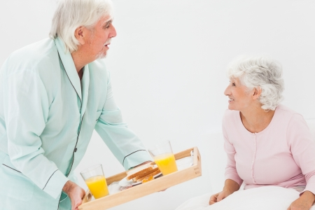 bringing: Elderly husband bringing wife breakfast in bed