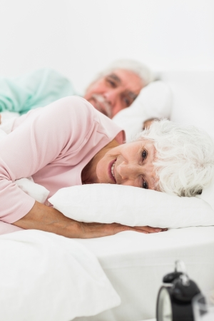 Elderly couple waking up in bedroom photo