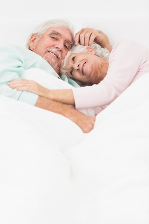 Elderly couple having a cuddle in bed Stock Photo - 18118260