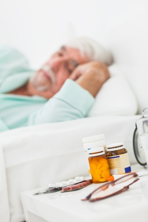 bedside table: Bedside table with pills and glasses with elderly man sleeping behind