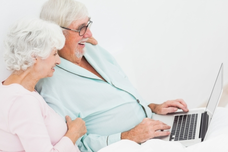Elderly couple with laptop in bed Stock Photo - 18118392