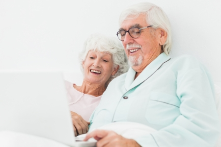 Elderly couple watching something on laptop in bed  Stock Photo - 18118379