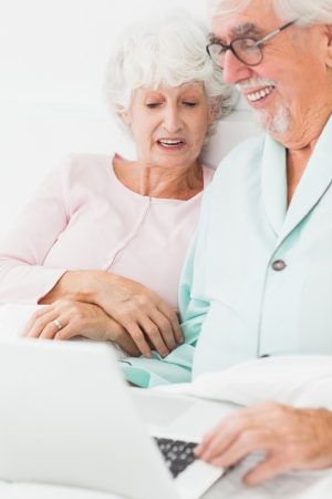 Smiling old couple using laptop in bed photo