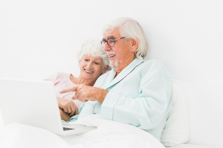 Happy elderly couple using laptop in bed Stock Photo - 18118376