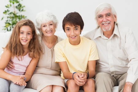 Happy grandparents with grandchilden on sofa Stock Photo - 18118399