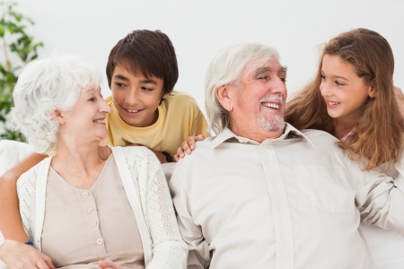 Grandparents with grandchildren on the couch talking and smiling Stock Photo - 18118387