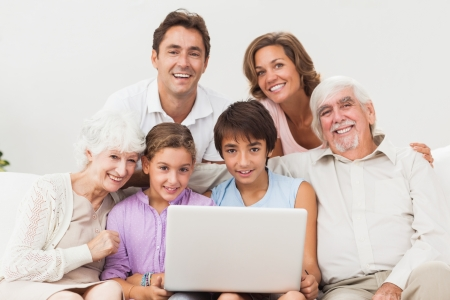 Multi-generation family on couch with laptop photo