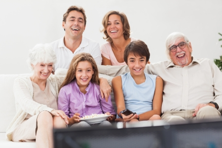 Familia extensa viendo la televisión juntos en el sofá