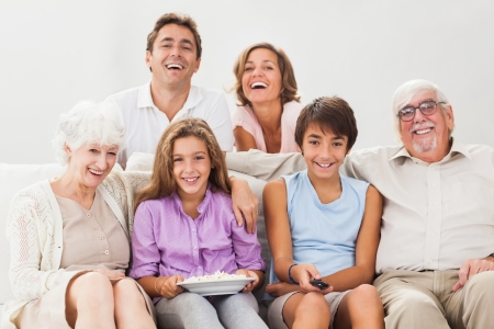 abode: Multi generation family on couch watching tv and smiling Stock Photo