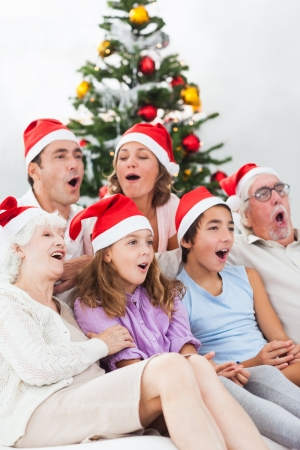 Extended family singing christmas carols together on couch photo