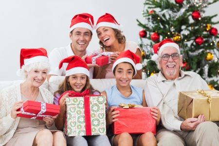 Happy family exchanging gifts at christmas time on the couch Stock Photo - 18118417