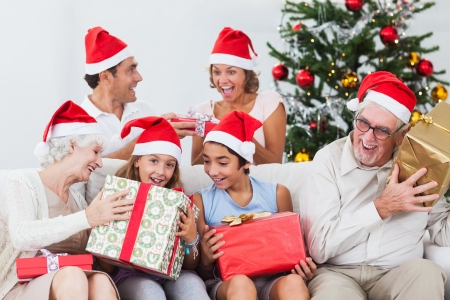 Excited family swapping christmas presents on the couch Stock Photo - 18118446