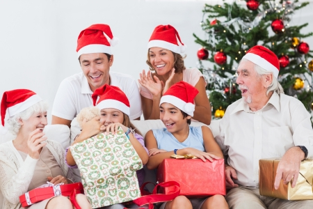 Little girl opening christmas present on couch with family photo