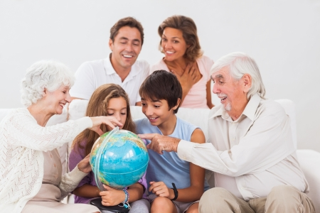 Extended family looking at globe on couch photo