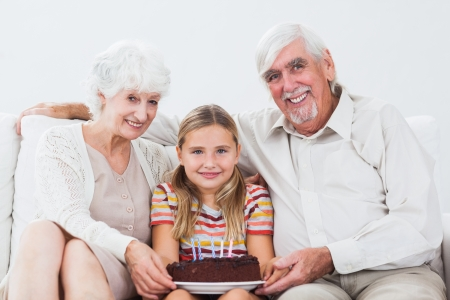Little girl celebrating birthday with grandparents with cake on the couch photo