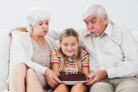 Little girl and grandparents blowing out the candles on birthday cake on couch photo