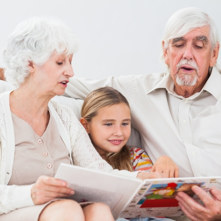 Little girl reading with grandparents on the couch photo