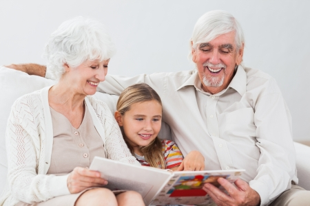 Happy little girl reading with grandparents on the couch photo