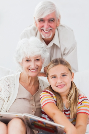 Little girl smiling with grandparents on the couch with a book photo