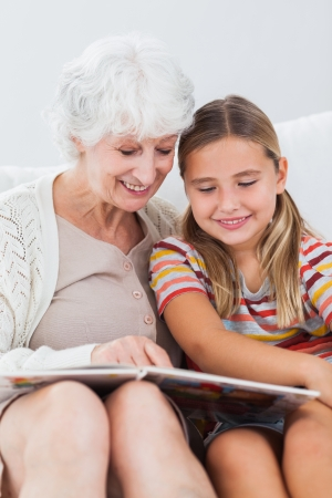 Little girl sitting on couch reading with granny photo