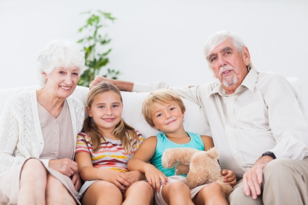 Smiling children with their grandparents on the couch Stock Photo - 18118512
