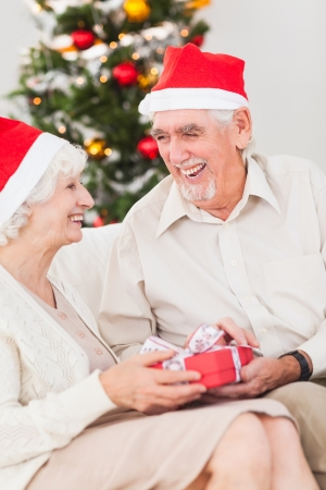Elderly couple exchanging christmas gifts on couch photo