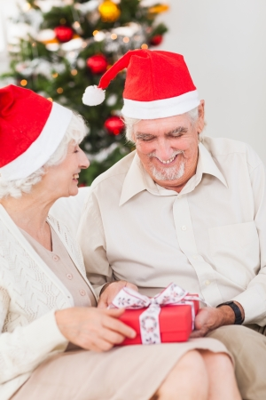 swapping: Elderly couple swapping christmas presents on the couch