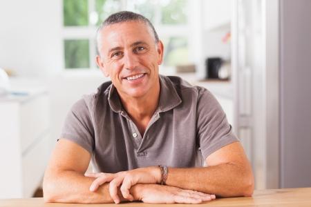 uomo felice: Felice l'uomo seduto a tavola in cucina