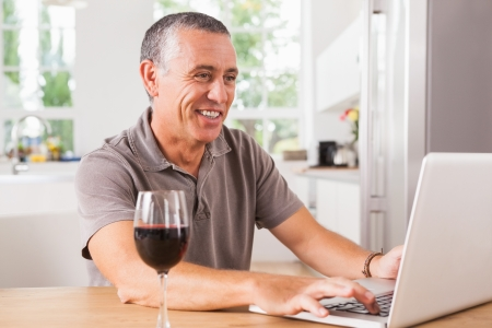 Happy man using laptop with glass of red wine at kitchen table photo