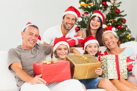 Happy family at christmas holding gifts on the couch photo