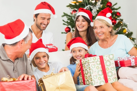 receive: Happy family at christmas swapping gifts on the couch Stock Photo
