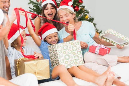 Happy family at christmas opening gifts together on the couch photo