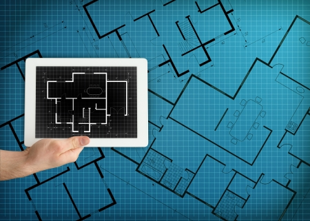 Tablet displaying blueprint on blue digital background photo