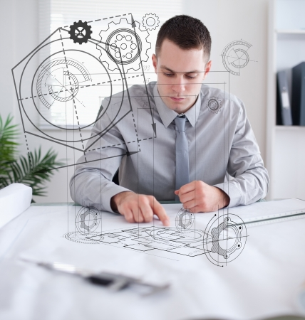 Architect at work in office with plan graphic photo