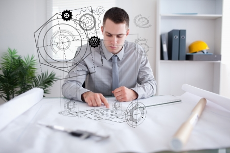 architect office: Architect planning out house in office with design graphics