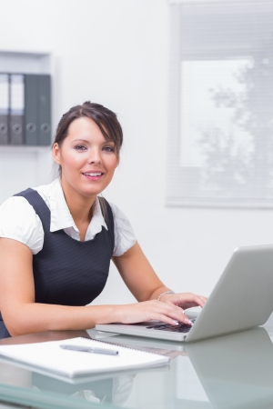 Woman working on her computer with smile at the office Stock Photo - 18118898