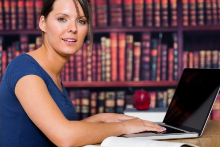 Woman smiling with computer in the college library photo