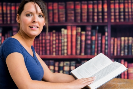 Girl smiling with book in the library photo
