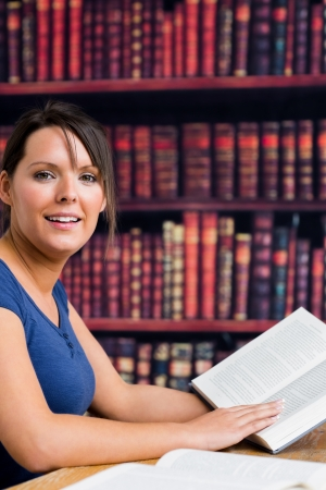 Woman smiling with book in college library photo