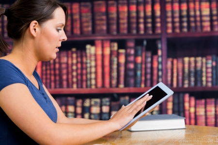 Woman touching tablet at library desk photo